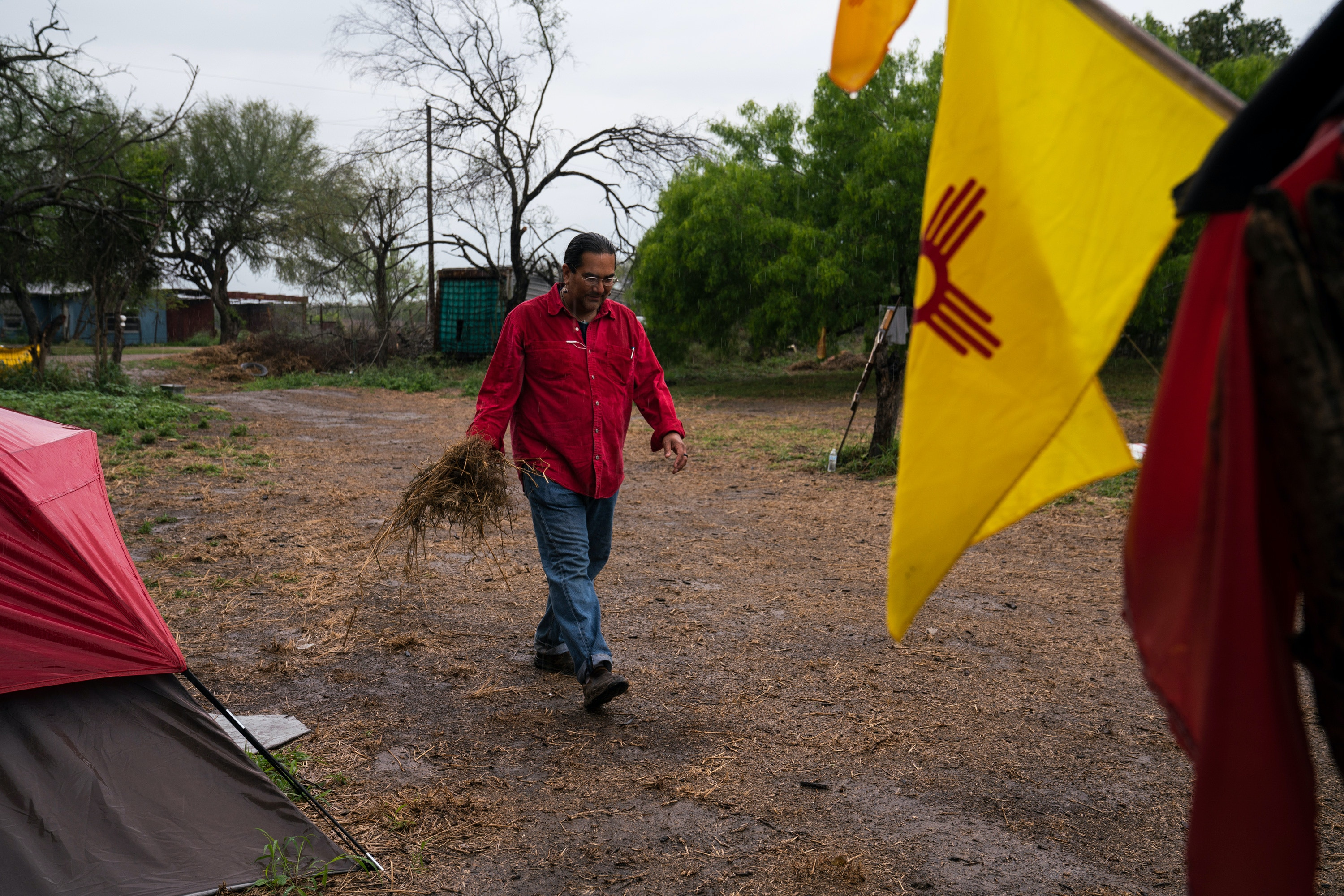 Christopher Basaldú, PhD in anthropology, collects grass to place it outside of his tent to clean up the mud from his shoes at Yalui Village in Hidalgo County, Texas on March 19, 2019. Basaldú has been camping for two months in anticipation of the border wall being built. Photo: Verónica G. Cárdenas for The Intercept