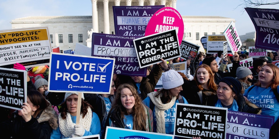 Pro-choice activists hold signs in response to anti-abortion activists participating in the