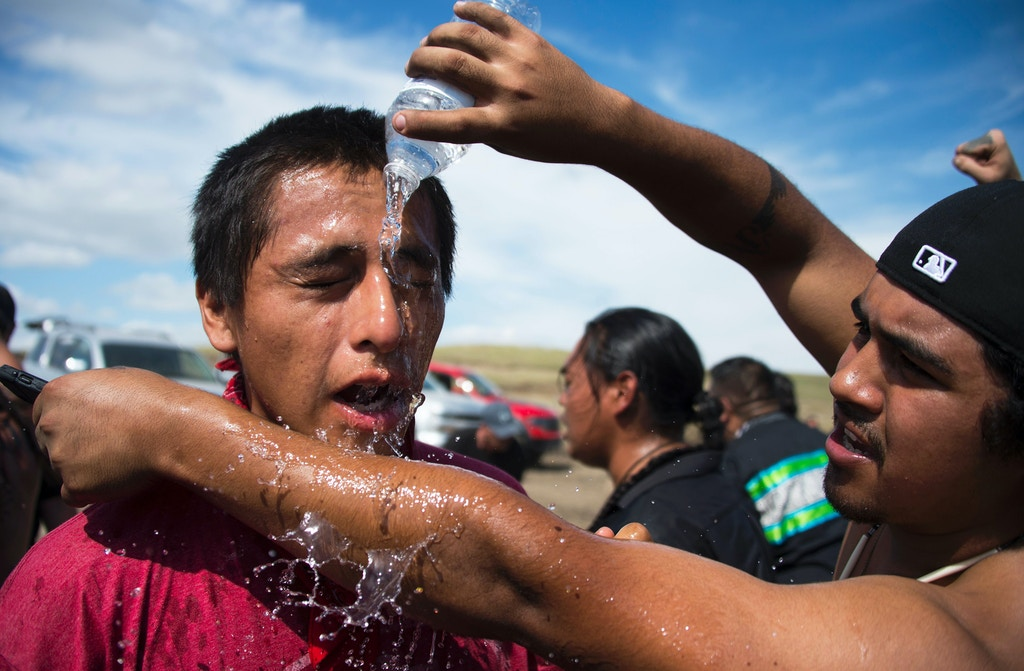 A protestor is treated after being pepper sprayed by private security contractors on land being graded for the Dakota Access Pipeline (DAPL) oil pipeline, near Cannon Ball, North Dakota, September 3, 2016.  Hundreds of Native American protestors and their supporters, who fear the Dakota Access Pipeline will polluted their water, forced construction workers and security forces to retreat and work to stop. / AFP / Robyn BECK        (Photo credit should read ROBYN BECK/AFP/Getty Images)