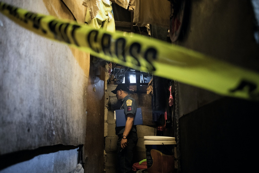 "A policeman investigates the scene where the body of an alleged drug user lies dead at a slum area in Manila after unidentified assailants killed him on December 8, 2017. Philippine President Rodrigo Duterte on December 5 told human rights groups criticising his deadly anti-drug war to ""go to hell"" after ordering police back to the frontlines of the crackdown.  Duterte had removed the police less than two months ago in response to rising opposition to the campaign. But his spokesman said he was now reinstating them because drug crimes had risen in their absence. / AFP PHOTO / NOEL CELIS        (Photo credit should read NOEL CELIS/AFP/Getty Images)"