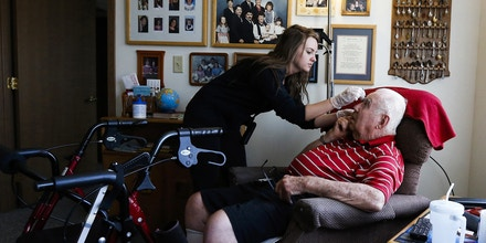 In a Monday, July 31, 2017 photo, nurse technician Brittani Peterman gives eye drops to resident Everett Beck in his apartment at Shorewood Senior Campus in Rochester, Minn. More and more elderly people now opt for care delivered in their homes, rather than at nursing homes. That has led to an explosion need for home health aides. (Andrew Link/The Rochester Post-Bulletin via AP)