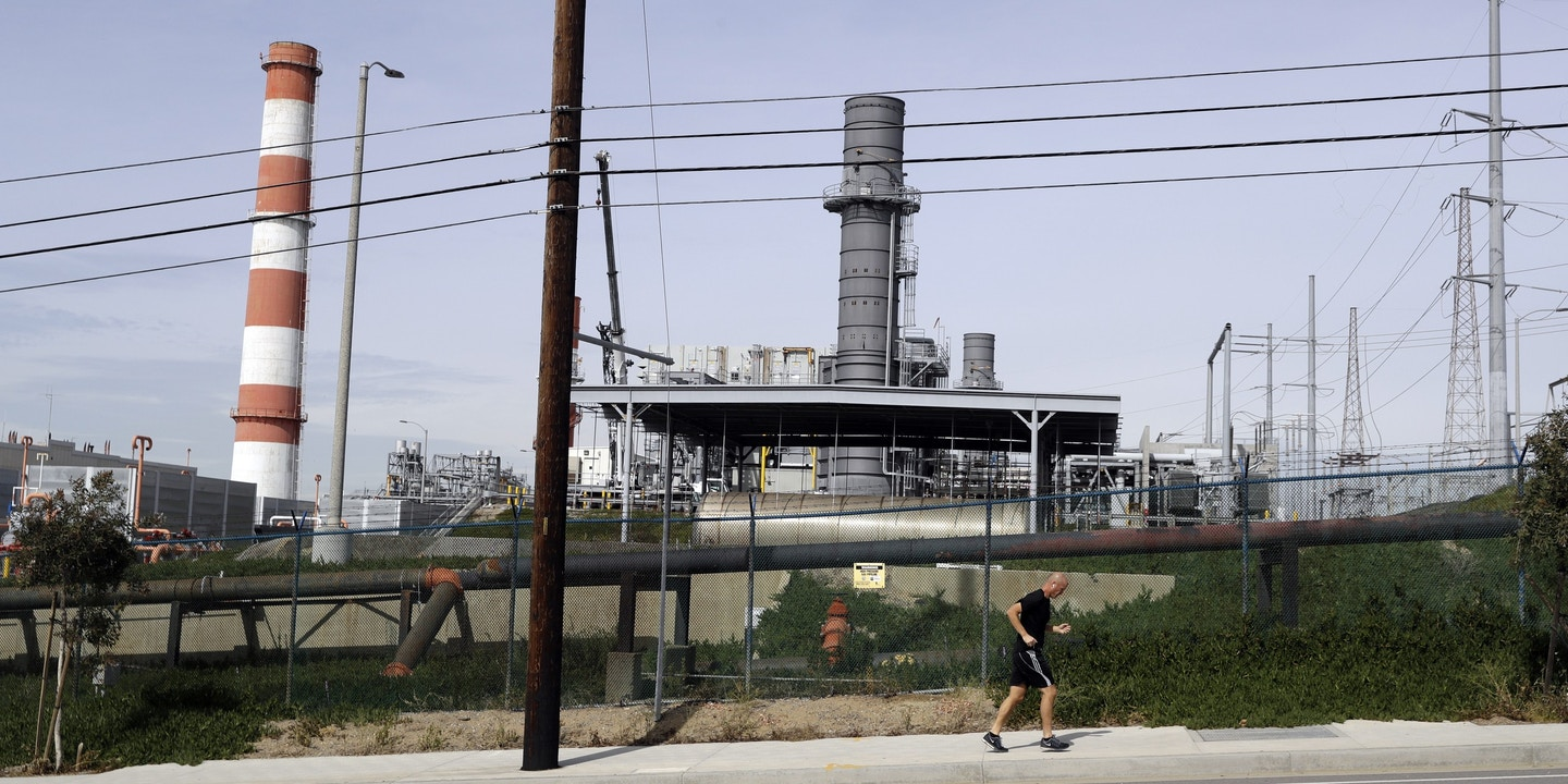 A jogger runs past the Scattergood power plant Tuesday, Feb. 12, 2019, in Los Angeles. Los Angeles will abandon a plan to spend billions of dollars rebuilding three natural gas power plants as the city moves toward renewable energy, Mayor Eric Garcetti said Monday. (AP Photo/Marcio Jose Sanchez)