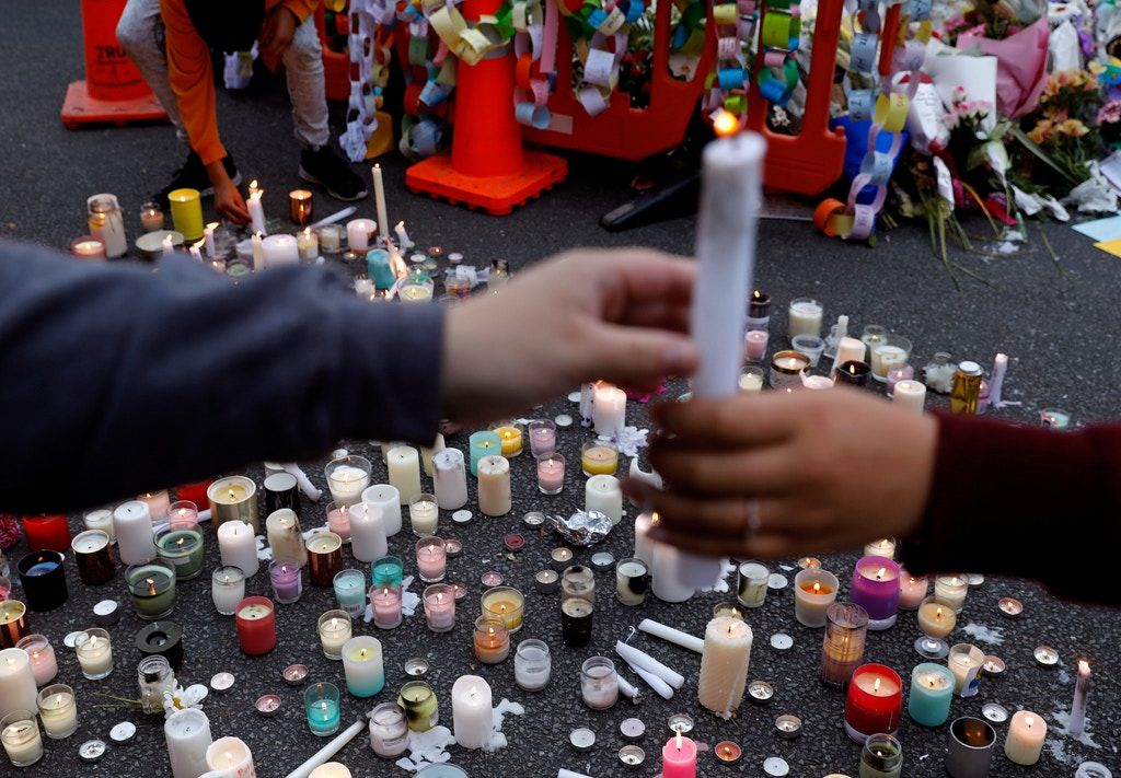 Students light candles as they gather for a vigil to commemorate victims of Friday's shooting, outside the Al Noor mosque in Christchurch, New Zealand, Monday, March 18, 2019. Three days after Friday's attack, New Zealand's deadliest shooting in modern history, relatives were anxiously waiting for word on when they can bury their loved ones.(AP Photo/Vincent Yu)