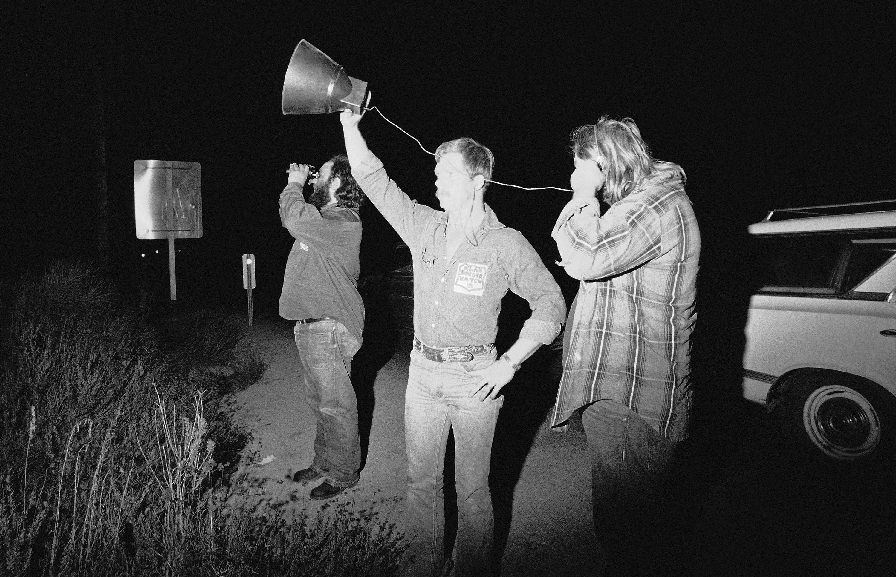 Three members of the Ku Klux Klan use a telescopic listening device and binoculars near the California-Mexico border in their search for illegal aliens entering the country in Dulzura on Tuesday, Oct. 26, 1977. Dennis Campbell, center, holds the listening instrument as Jim Shea, left, scans the hilltops for movement in the bright moonlight. The man at right refused to be identified. (AP Photo/Harold Valentine)