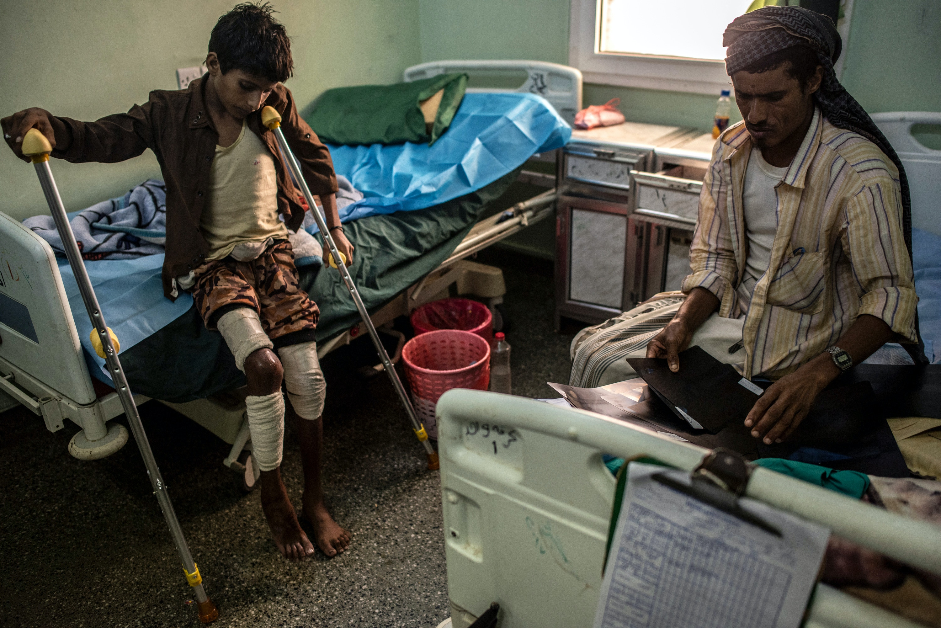 ADEN, YEMEN - SEPTEMBER 23: Humedan Hussin Abdullah, sits with father at a government hospital bed on September 23, 2018 in Aden, Yemen. Abdullah is waiting in the hospital to have shrapnel removed from his leg, an injury he sustained in Hodeidah province that killed two of his family members. A coalition military campaign has moved west along Yemen's coast toward Hodeidah, where increasingly bloody battles have killed hundreds since June, putting the country's fragile food supply at risk. (Photo by Andrew Renneisen/Getty Images)