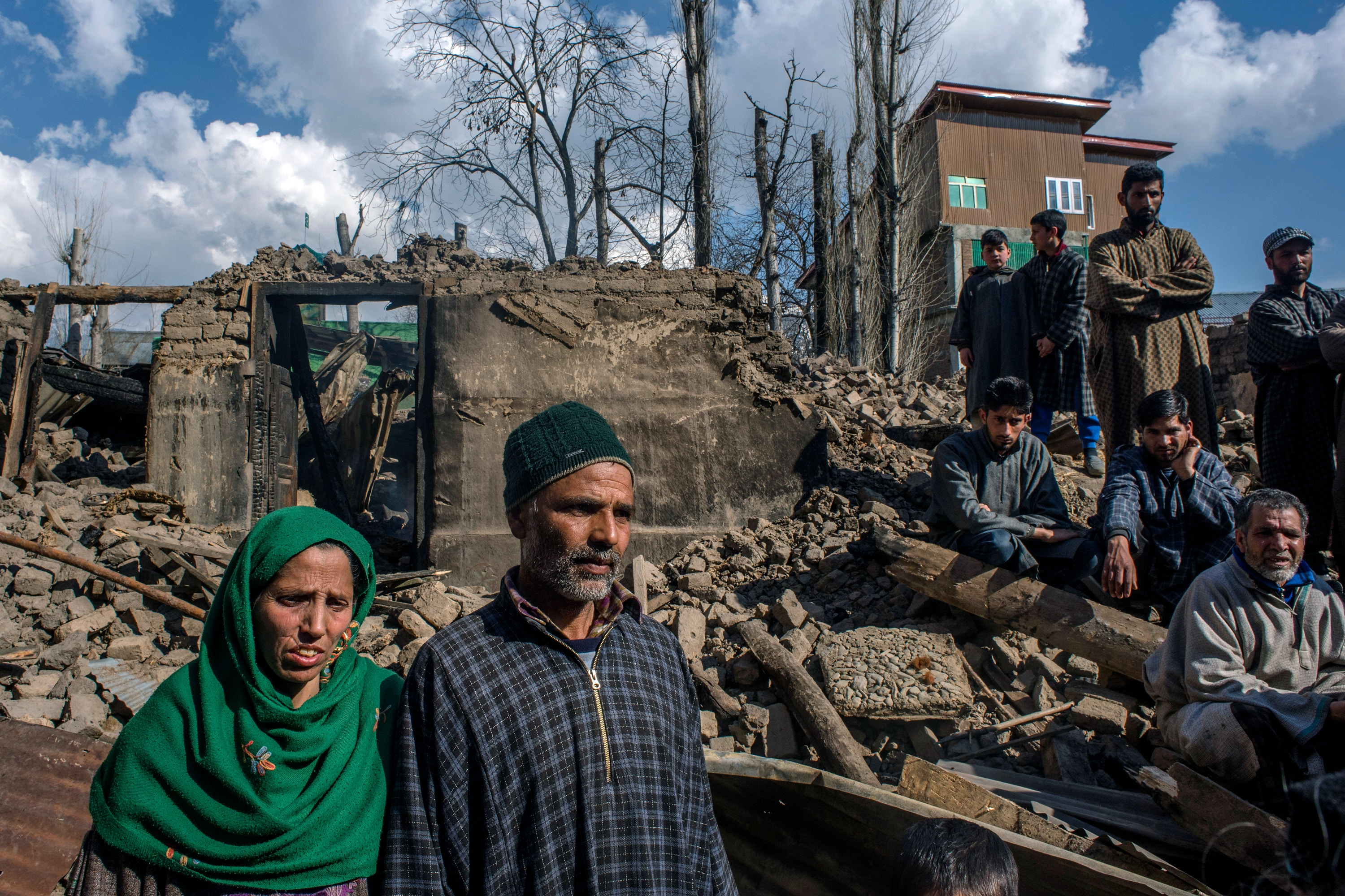 TRAL, KASHMIR, INDIA - MARCH 6: Saleema Begum and her husband Ghulam Qadir Naikoo, stand in front the rubble of their residential house, which was destroyed in a gun battle between Indian government forces and local rebels on March 6, 2019 in Tral, south of Srinagar, the summer capital of Indian administered Kashmir, India. Two Kashmiri rebels were killed yesterday, and a residential house destroyed in a gun battle with Indian government forces  and rebels. Indian government forces continued their operation against militants fighting against Indian rule and for the independence of Kashmir from Indian, in the wake of the February 14 suicide attack that killed over 40 Indian paramilitary troopers. Two rebels of Hizbul Mujahideen outfit were killed in a gun battle yesterday with Indian forces in South Kashmirs Pulwama district. Both militants were locals. Since the Pulwama attack, 15 militants have been killed in six separate gun fights in Indian administered Kashmir. Twelve Indian government forces personnel were killed during the operations, while two civilians also lost their lives.  (Photo by Yawar Nazir/Getty Images)