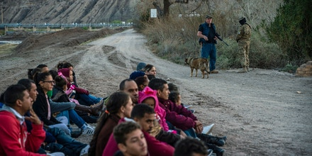 TOPSHOT - Propery owner Jeff Allen, 56, (rear left) stands near a group of about 30 Brazilian migrants, who had just crossed the border at his property in Sunland Park, New Mexico on the US-Mexico border on March 20, 2019, as they wait for US Border Patrol to pick them up. - The militia members say they will patrol the US-Mexico border near Mt. Christo Rey,