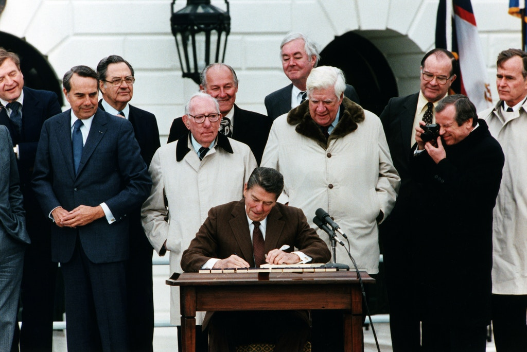 President Ronald Reagan signs the Social Security Act Amendment with Vice President George Bush (far r), Senator Bob Dole (2nd from l), and Congressmen Tip O'Neill (4th from r) and Daniel Moynihan (5th from r) on hand as witnesses. (Photo by © CORBIS/Corbis via Getty Images)