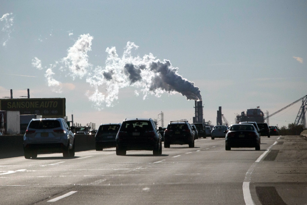 CARTERET, NJ - NOVEMBER 17: Vehicles move along the The New Jersey Turnpike Way while a Factory emits smoke on November 17, 2017 in Carteret, New Jersey. The United States is still contributing to the global greenhouse gas emissions as the Trump Administration has dismantled the U.S. foreign-policy to reduce carbon pollution. Political divisions in the United States over climate change have spilled over to the outside world as seen at the COP23 United Nations Climate Change Conference that ends today in Bonn, Germany. (Photo by Kena Betancur/VIEWpress/Corbis via Getty Images)