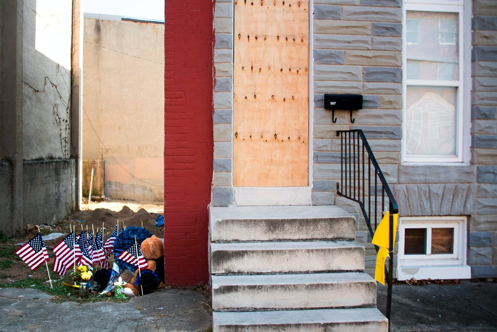 A memorial for Baltimore Police Detective Sean Suiter, who was fatally shot while investigating a previous killing in West Baltimore earlier this month, sits in an alley in where he was slain in west Baltimore, Maryland, on November 29, 2017. / AFP PHOTO / JIM WATSON        (Photo credit should read JIM WATSON/AFP/Getty Images)