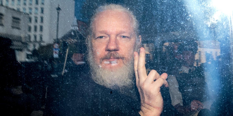 Julian Assange gesticula para a mídia de um veículo da polícia em sua chegada ao Tribunal Magistrados de Westminster, em 11 de abril de 2019 em Londres.