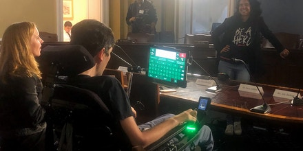 On April 29, 2019, Ady Barkan, center, demonstrates the device he will be using to testify the following day at the House Rules Committee hearing on the Medicare for All Act.