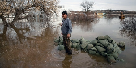 Henry Red Cloud wades through floodwaters on his property on the Pine Ridge Indian Reservation in South Dakota, March 22, 2019. On Pine Ridge, extreme weather and bad roads have set off a humanitarian disaster that seems unlikely to abate soon. (Kristina Barker/The New York Times)