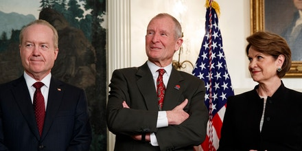Raytheon CEO Tom Kennedy, left, former Director of National Intelligence Dennis Blair, center, and Lockheed Martin CEO Marillyn Hewson wait for the arrival of President Donald Trump to an event announcing tariffs and investment restrictions on China, in the Diplomatic Reception Room of the White House, Thursday, March 22, 2018, in Washington. (AP Photo/Evan Vucci)