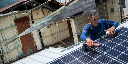 Julio Rosario installs solar panels at a home in Adjuntas, Puerto Rico, on July 24, 2018.