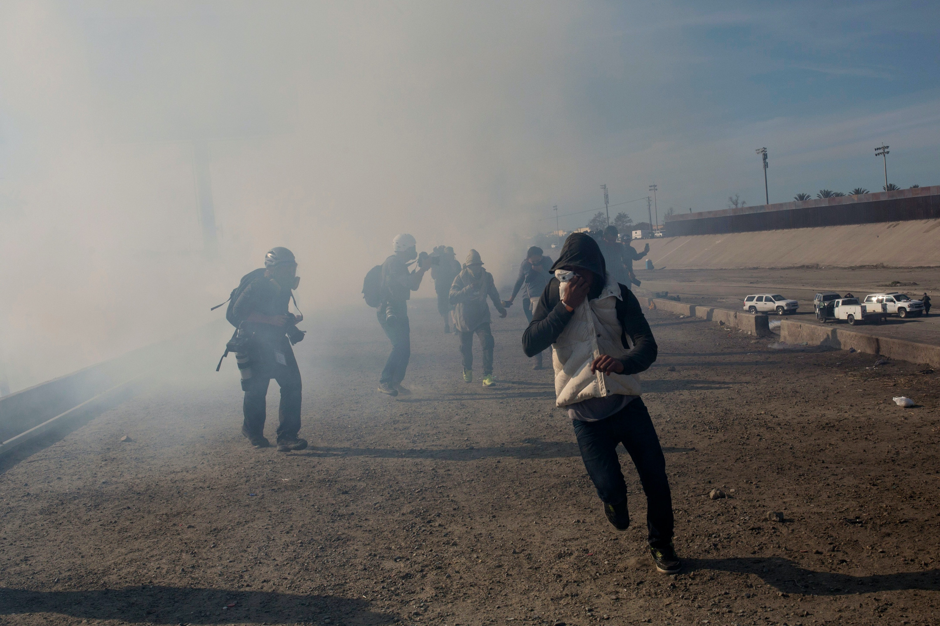 FILE - In this Nov. 25, 2018, file photo, migrants run from tear gas launched by U.S. agents, amid photojournalists covering the Mexico-U.S. border, after a group of migrants got past Mexican police at the Chaparral crossing in Tijuana, Mexico. Children torn from their parents, refugees turned away, tear gas fired on asylum-seekers, and a swath of the globe derided by the president in crude language. In a breathless 2018, they were just a handful of headlines on immigration, one of the year's most dominant issues. (AP Photo/Rodrigo Abd, File)