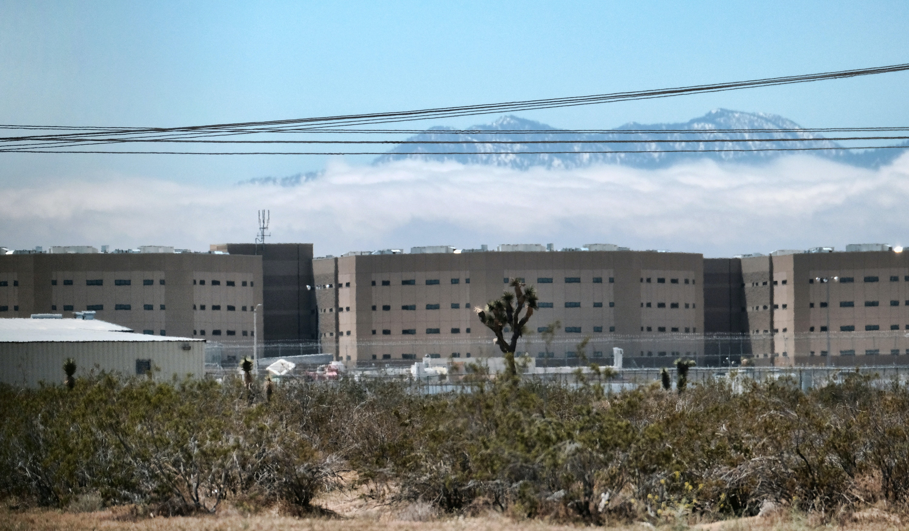 This Saturday April 20, 2019 photo shows the Adelanto Detention Center in Adelanto, Calif., a desert community northeast of Los Angeles. For nearly eight years, Adelanto has joined with a private prison company and federal officials to run California's largest immigration detention facility. Now, the city of Adelanto is backing out of its contract to run the 1,900 bed facility amid complaints of shoddy conditions and inadequate medical care. But ending the deal won't necessarily shutter the center and rather, could pave the way for its expansion. (AP Photo/Richard Vogel)