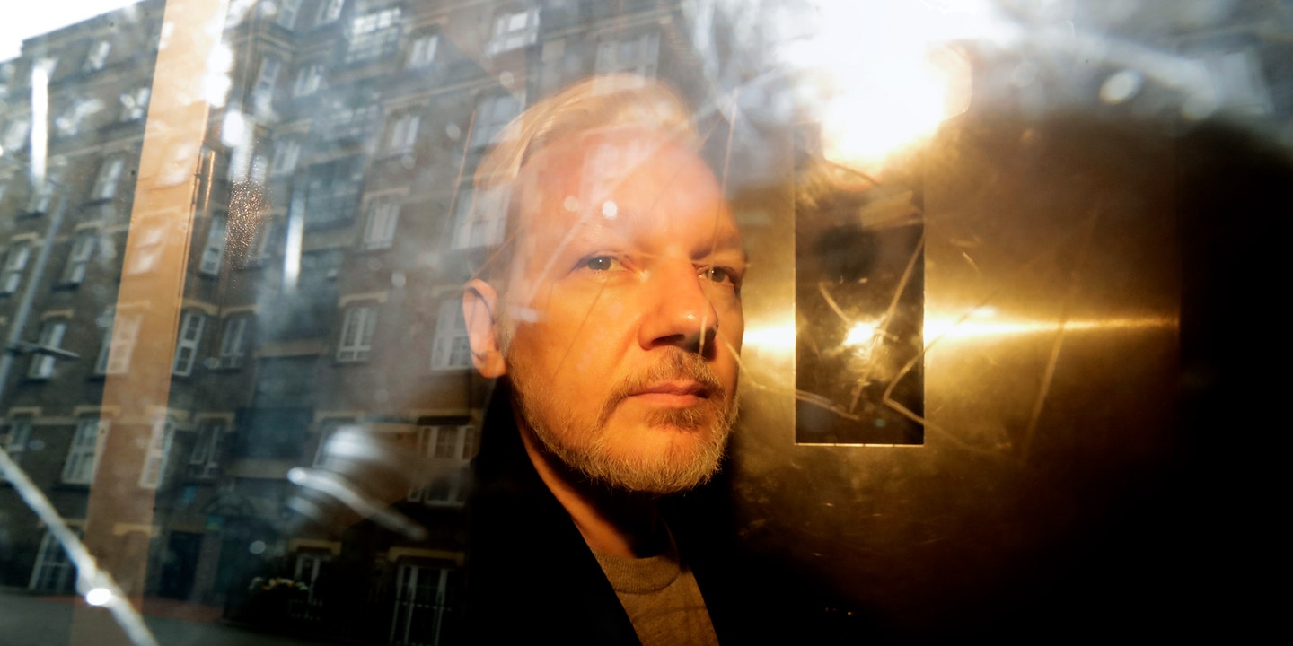 Buildings are reflected in the window as WikiLeaks founder Julian Assange is taken from court, where he appeared on charges of jumping British bail seven years ago, in London, Wednesday May 1, 2019. Assange has been jailed for 50 weeks for breaching his bail after going into hiding in the Ecuadorian embassy in London.(AP Photo/Matt Dunham)