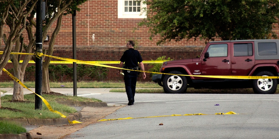 A police officer walks at the scene where eleven people were killed during a mass shooting at the Virginia Beach city public works building, Friday, May 31, 2019 in Virginia Beach, Va. A longtime, disgruntled city employee opened fire at a municipal building in Virginia Beach on Friday, killing 11 people before police fatally shot him, authorities said.  Six other people were wounded in the shooting, including a police officer whose bulletproof vest saved his life, said Virginia Beach Police Chief James Cervera. (L. Todd Spencer/The Virginian-Pilot via AP)