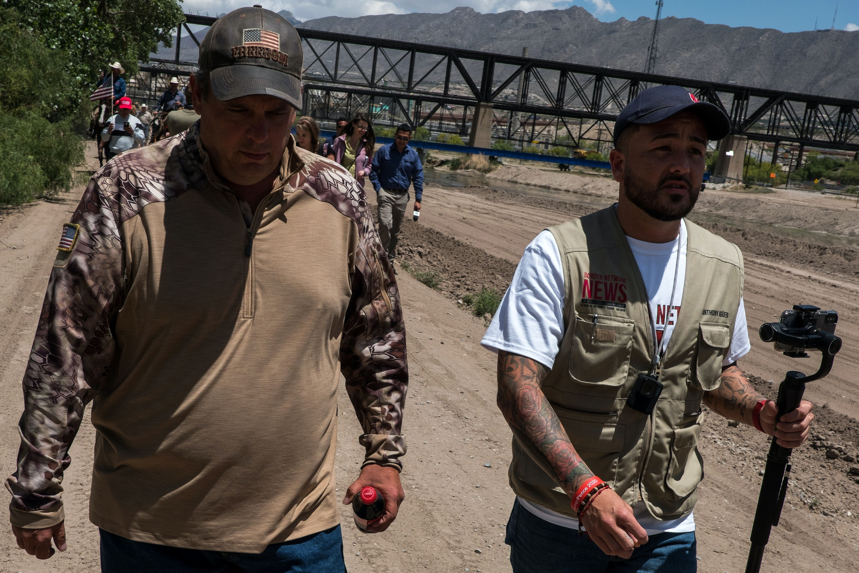 Jim Benvie, spokesman for the newly-named Guardian Patriots, left, and Anthony Agüero walk along the banks of the Rio Grande nearby the U.S.-México border on the outskirts of Sunland Park, New Mexico, Saturday, May 11, 2019. (Joel Angel Juárez for The Intercept)