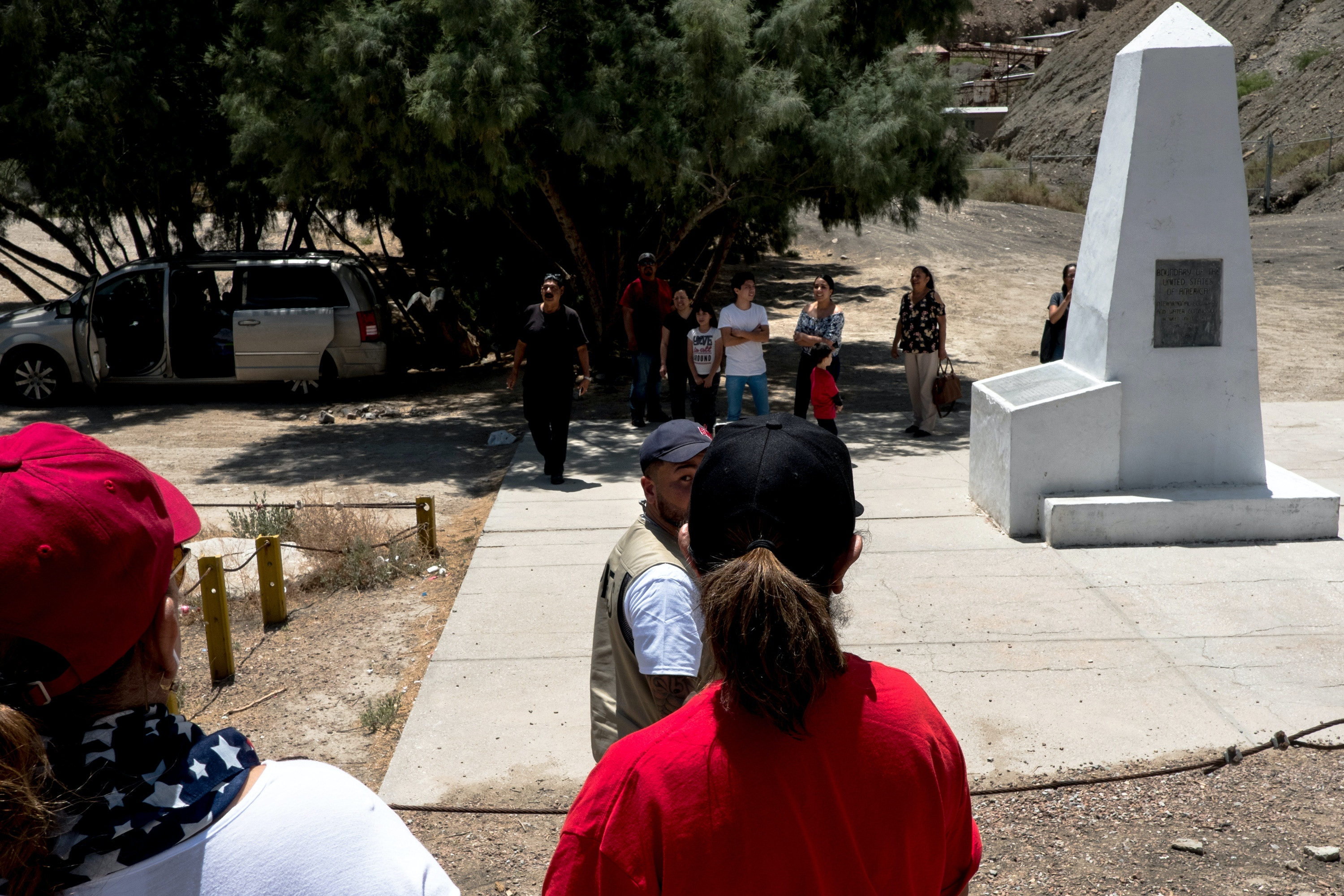 Anthony Agüero glances back at Jennifer Phelps, left, and Nancy Esquivel of El Paso, right, as he heads over to speak to Mexican nationals at Monument One along the U.S.-México border on the outskirts of Sunland Park, New Mexico, Saturday, May 11, 2019. (Joel Angel Juárez for The Intercept)