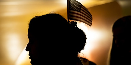 A newly naturalized U.S. citizen wears an American flag in her hair during a ceremony  on Feb. 13, 2019.