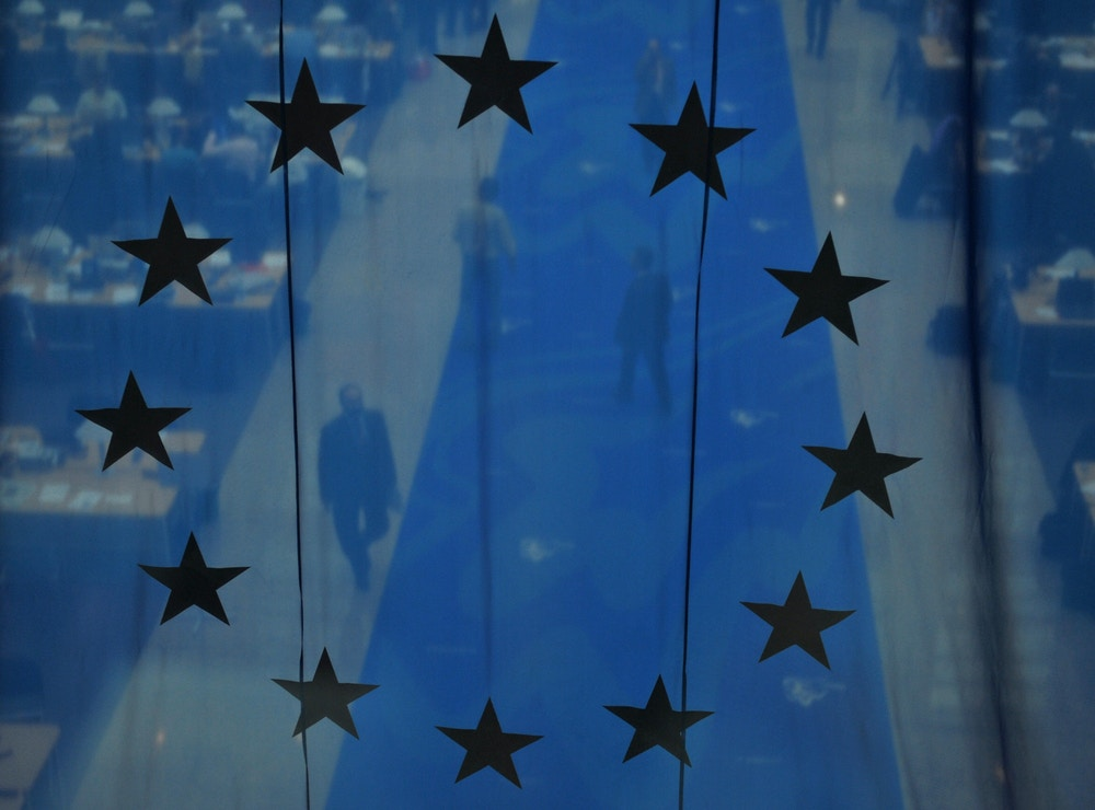 "A press room is seen through an EU flag during a European Summit at the headquarters of the European Council on March 14, 2008 in Brussels. EU leaders backed ambitious targets to cut energy use and fight climate change but stressed that the package must not involve ""excessive costs"" amid an economic downturn. AFP PHOTO / DOMINIQUE FAGET (Photo credit should read DOMINIQUE FAGET/AFP/Getty Images)"
