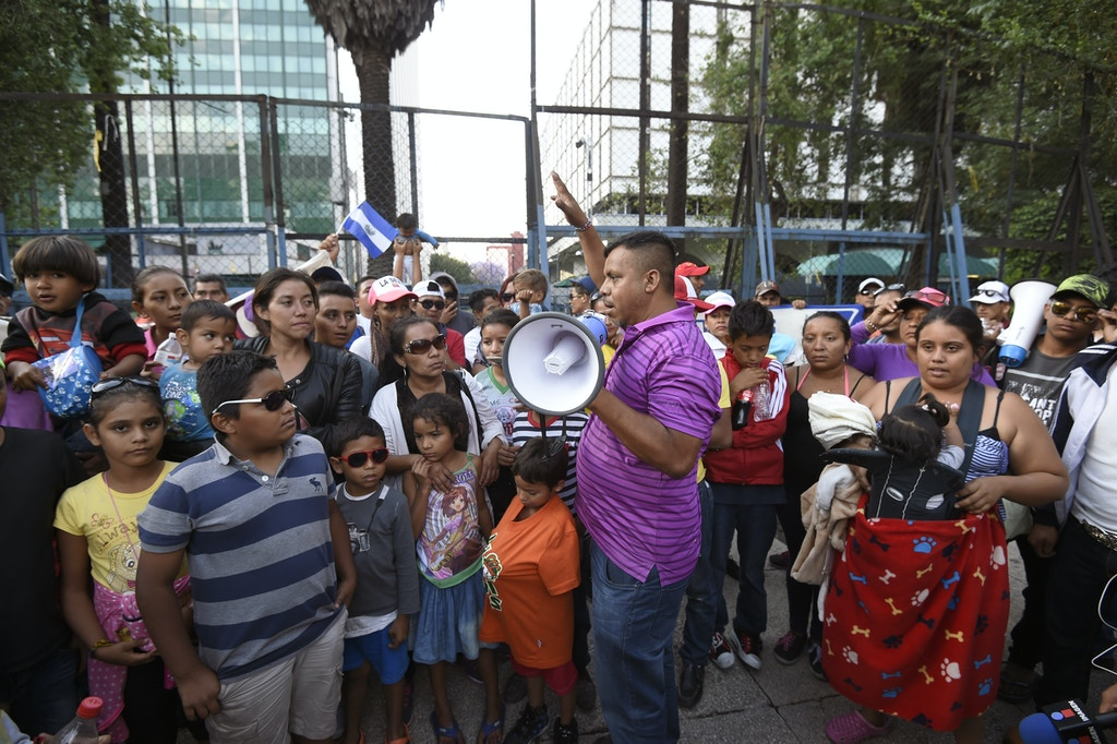 "Honduran leader of the ""Migrant Viacrucis"" caravan, Irineo Mujica (C), speaks during a protest outside the US Embassy in Mexico City, on April 12, 2018.  The caravan, which prompted fury from US President Donald Trump, assembled on the border with Guatemala on March 25 but started breaking up in southern Mexico after organizers said it had abandoned its goal of reaching the US border and would end its activities with the rally in Mexico City."