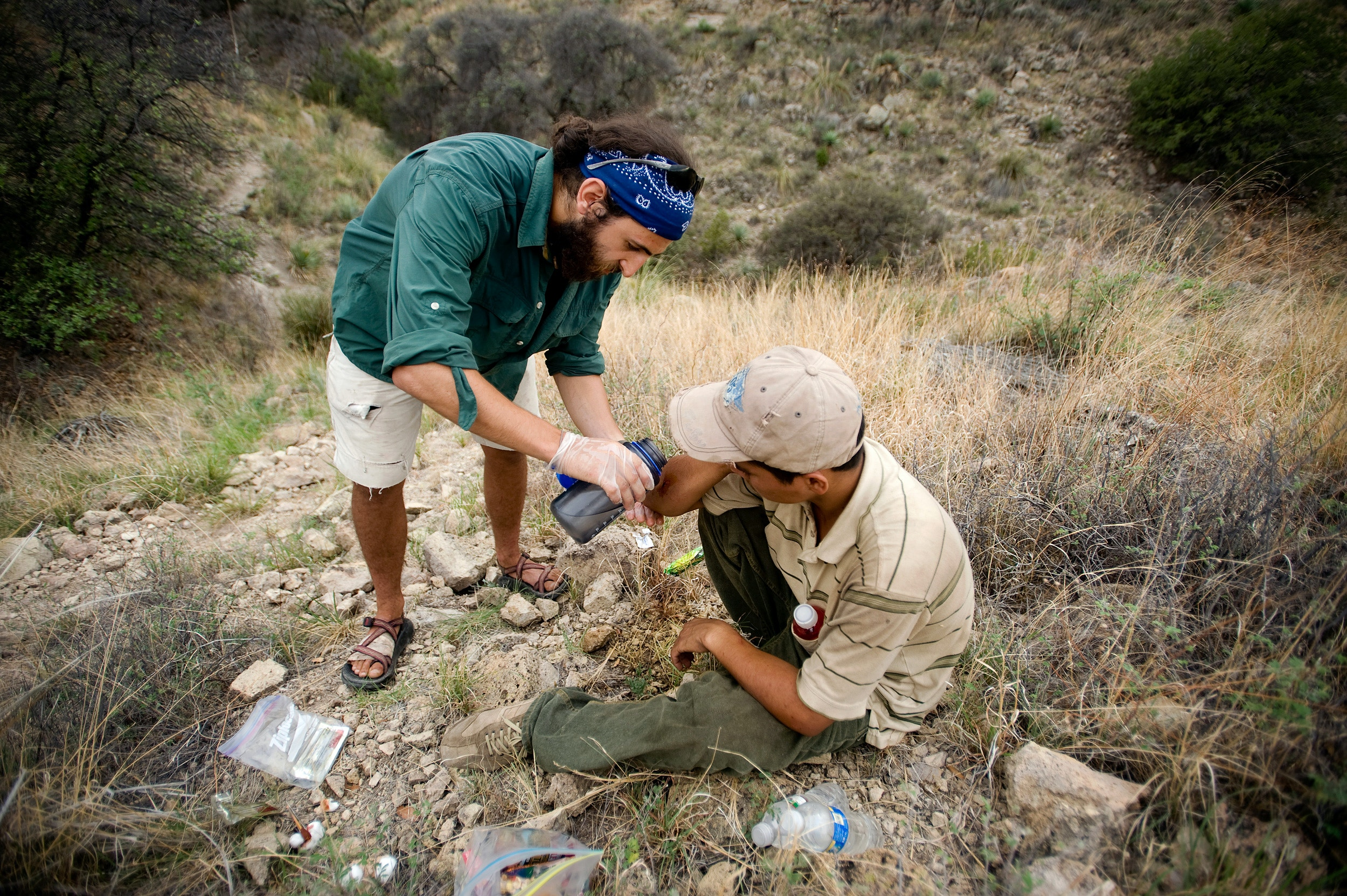 No More Deaths volunteer Jake Olzen tends to a knee injury on a migrant after an encounter during a water drop patrol near Apache Pass outside Arivaca, Arizona. No More Deaths help migrants suffering from dehydration, falls, sprained ankles, blisters, and other hazards commonly occurring from exposure in the desert.