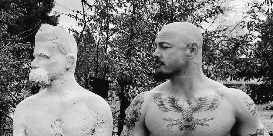 Jack Donovan posa ao lado de uma estátua de Nietzsche.
