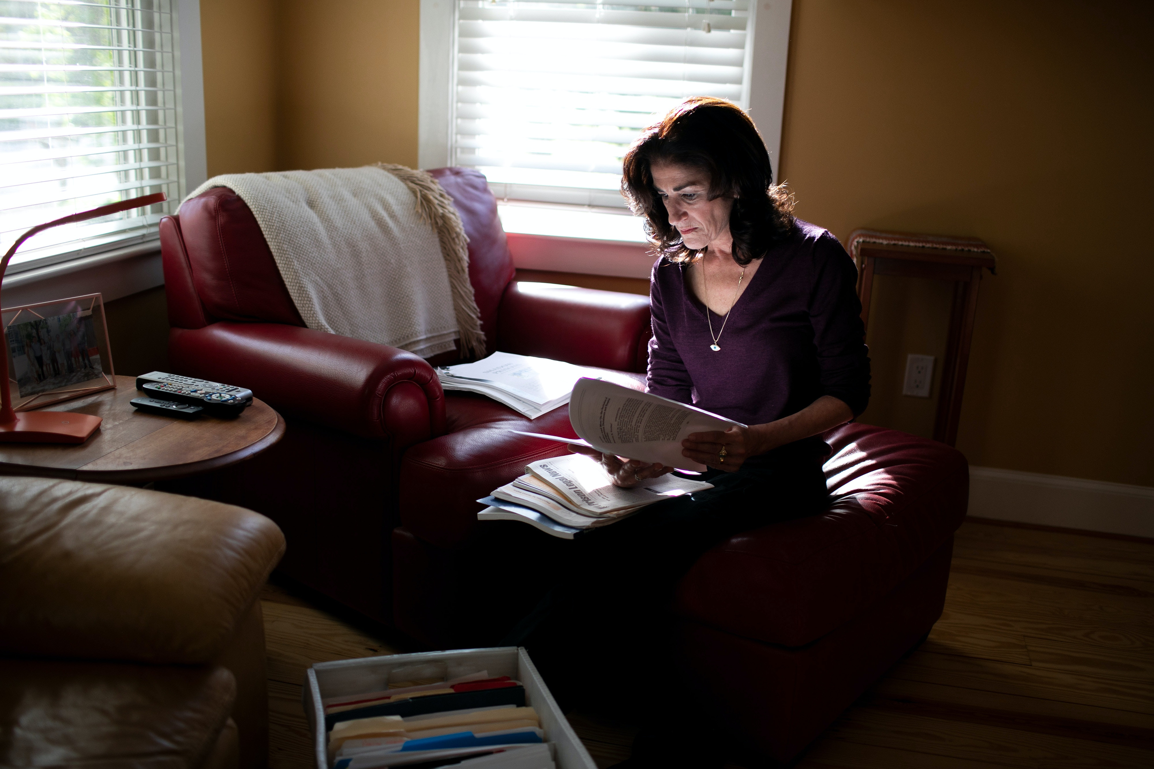 Mansfield, MA -- 05/08/2019 -- Ellen Gallagher looks through information about solitary confinement in her home office on May 8, 2019, in Mansfield, Massachusetts. This is part of a collection of information that she researched and used during the process of trying to understand the scope of the use of solitary confinement in immigration detention. (Kayana Szymczak for The Intercept)