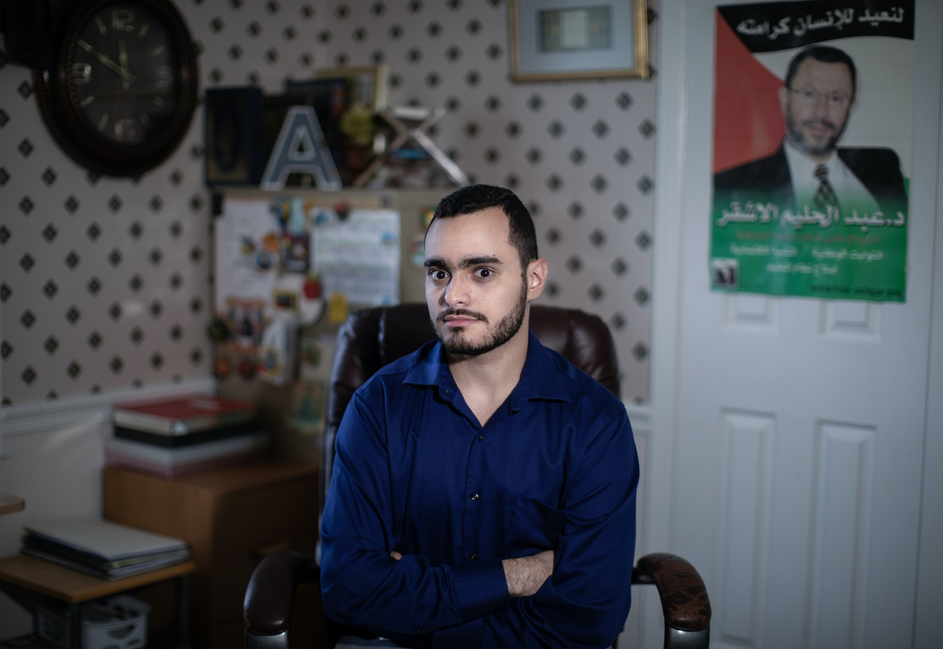 Ahmad, 23,  son of Abedlhaleem Ashqar, posing for a portrait with his father's photo in the background  at his house in Northern Virginia. Abdelhaleem Ashqar recently served 11 years in prison for refusing to testify to a grand jury investigating the Palestinian militant group Hamas.