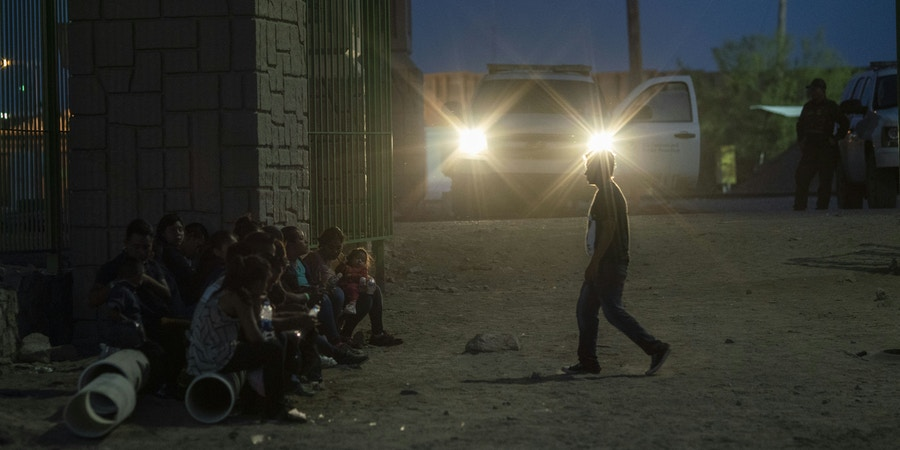 Migrants are pictured waiting to be taken to a processing facility near the Paso Del Norte International Bridge in Downtown El Paso, Texas on May 31, 2019. - The border area is bracing for the impact of what may happen after Trump unexpectedly announced his readiness to levy tariffs on all Mexican imports, beginning at five percent starting June 10 and rising monthly to as high as 25 percent until Mexico substantially reduces the flow of illegal immigration. (Photo by Paul Ratje / AFP)        (Photo credit should read PAUL RATJE/AFP/Getty Images)