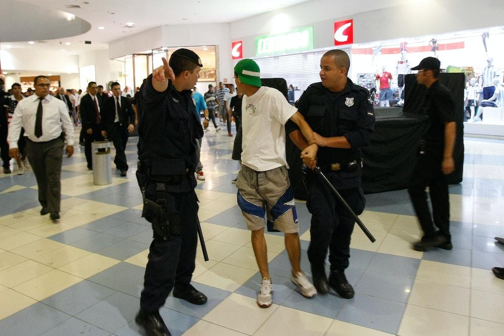 Em 2013, policiais retiram jovem do shopping Internacional de Guarulhos (SP). Após lojistas acionarem a polícia com denúncias de roubo, a PM prendeu 15 menores. Foto: Robson Ventura/Folhapress.