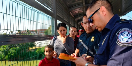 U.S. Customs and Border Protection agents process a Cuban family, whose turn had been called to apply for asylum, on a bridge between Nuevo Laredo, Mexico, and Laredo, Texas, on July 10, 2019.