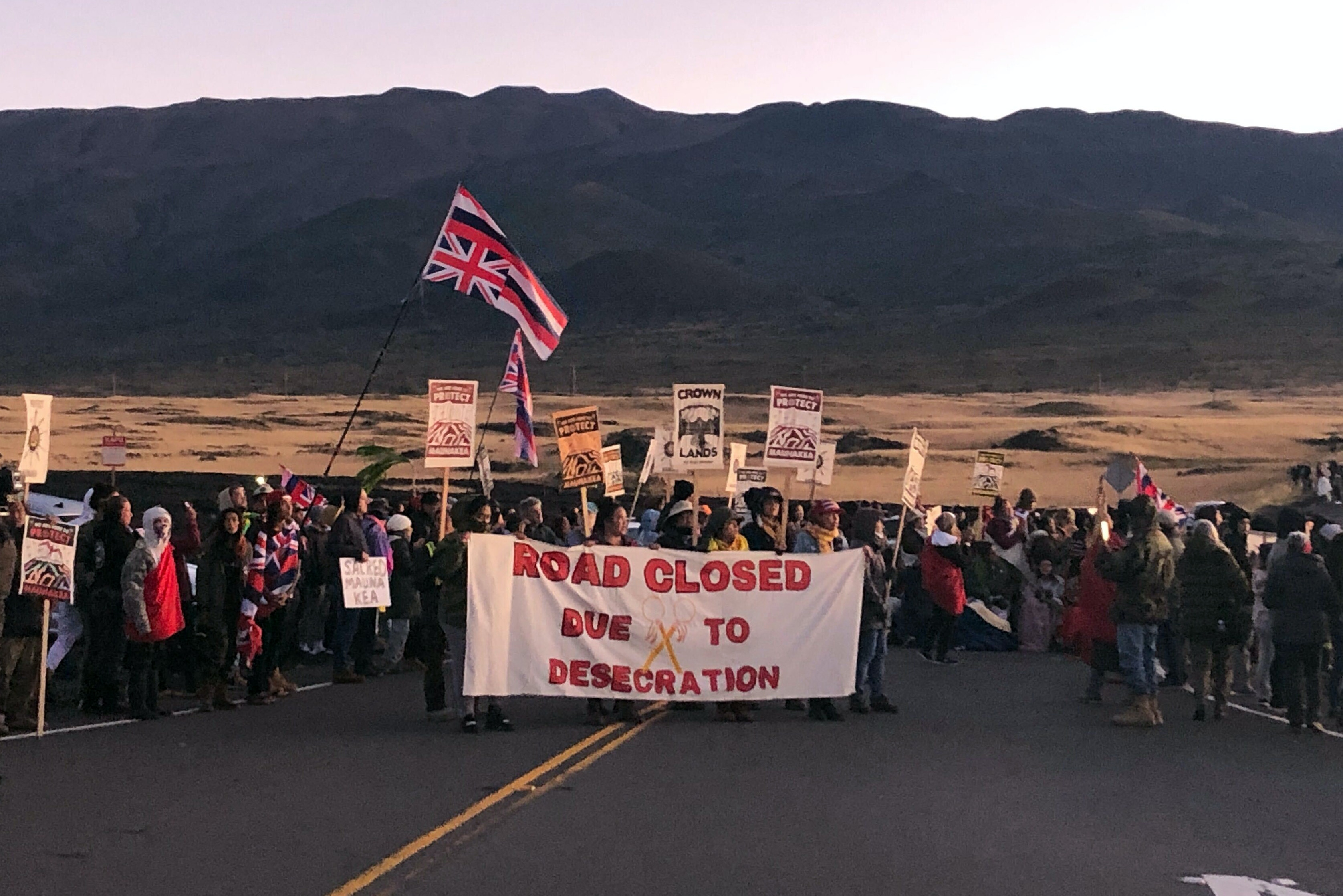 Demonstrators are gather to block a road at the base of Hawaii's tallest mountain, Monday, July 15, 2019, in Mauna Kea, Hawaii, to protest the construction of a giant telescope on land that some Native Hawaiians consider sacred. (AP Photo/Caleb Jones)