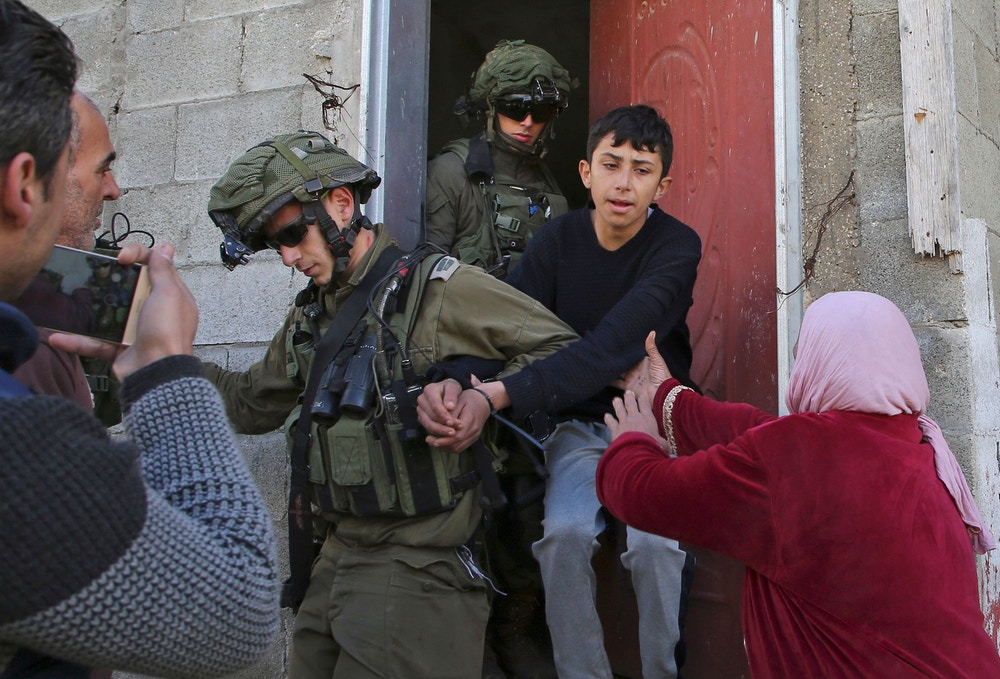 TOPSHOT - Israeli soldiers take into custody a Palestinian youth as Palestinian women protest, following a demonstration against the expropriation of Palestinian lands by Israel in the village of Kfar Qaddum, near Nablus in the occupied West Bank, on January 18, 2019. (Photo by Jaafar Ashtiyeh / AFP)        (Photo credit should read JAAFAR ASHTIYEH/AFP/Getty Images)