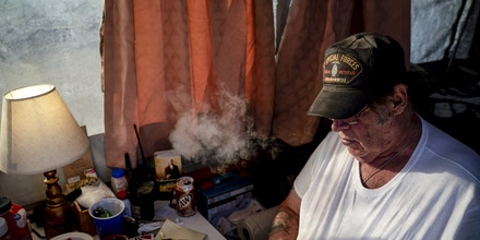 Striker, the leader of Constitutional Patriots New Mexico Border Ops Team militia, smokes a cigarrette inside the team's camper while discussing logistics on a group chat near the US-Mexico border in Anapra, New Mexico on March 20, 2019. - The militia members say they will patrol the US-Mexico border near Mt. Christo Rey,