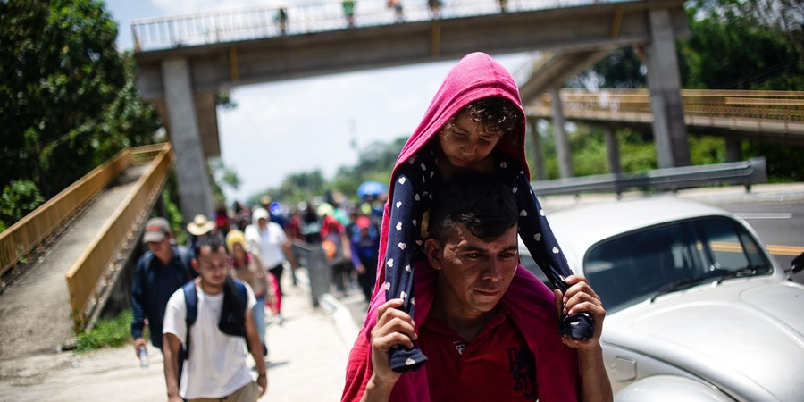 TOPSHOT - Central American migrants heading in caravan to the US rest beside the road between Metapa and Tapachula in Mexico on April 12, 2019. - A group of 350 Central American migrants forced their way into Mexico Friday, authorities said, as a new caravan of around 2,500 people arrived -- news sure to draw the attention of US President Donald Trump. Mexico's National Migration Institute said some members of the caravan had a