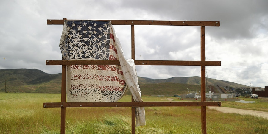 """OTAY MESA, CALIFORNIA - APRIL 03: An old billboard which displayed a U.S. flag stands on the U.S. side of the U.S.-Mexico border on April 3, 2019 in Otay Mesa, California. U.S President Trump told reporters last week """"there's a very good likelihood"""" that he will close the U.S. Southern border this week.  (Photo by Mario Tama/Getty Images)"""