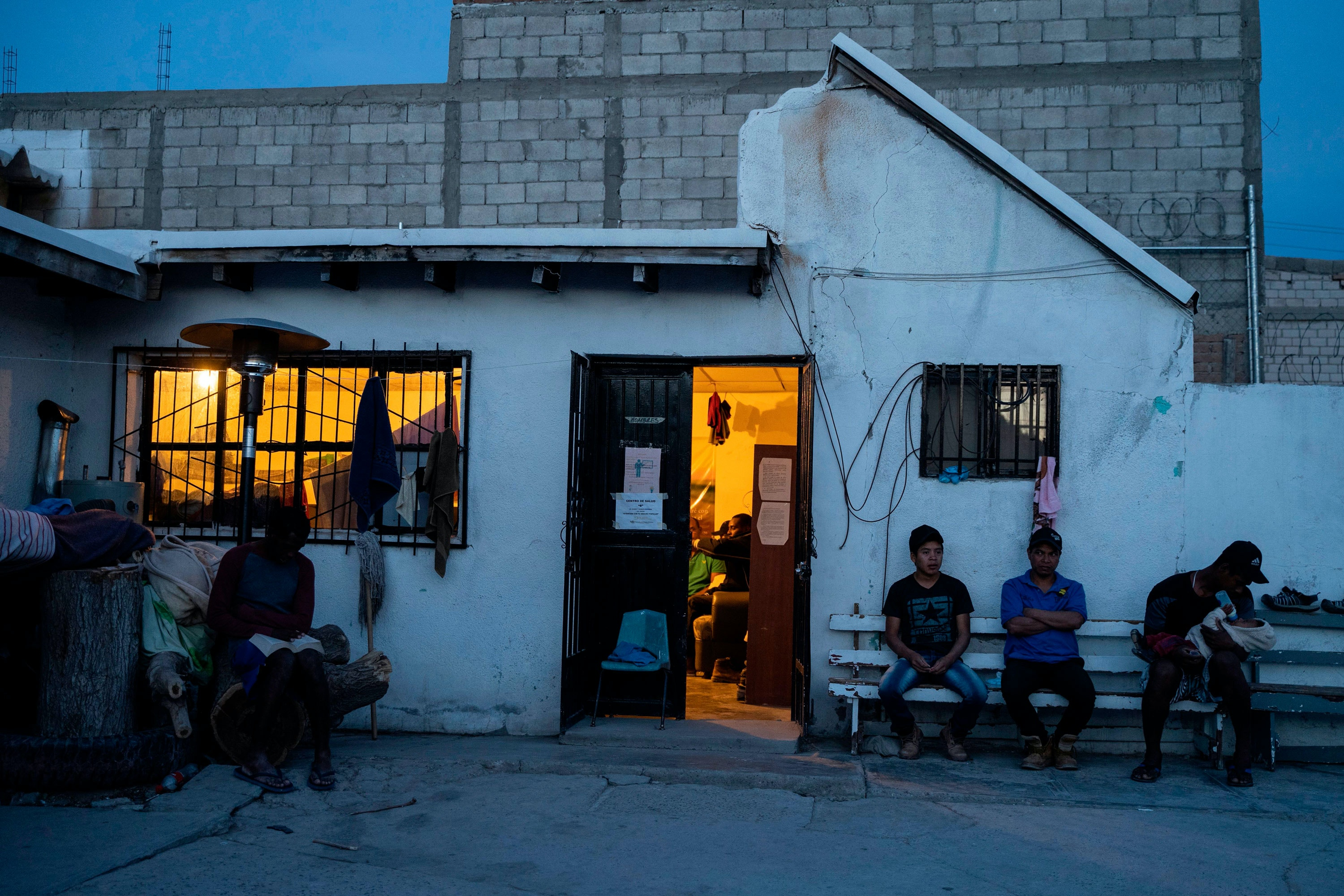 "Migrants waiting to enter the United States are pictured at dusk at Iglesia Metodista ""El Buen Pastor,"" a church run shelter for migrants, where they are being allowed to stay while they either wait for their number to be called on the metered system, or wait for their second asylum hearings, in Ciudad Juarez, Chihuahua State, on May 18, 2019. - About 7,000 migrants are waiting to enter the United States via El Paso, either by the metered number system, or those which are part of the remain in Mexico policy, Migrant Protection Protocols. Those that are part of MPP are made to wait out their asylum claims on the Mexican side of the Border, where they are vulnerable to criminals looking for an easy target, extortionists, corrupt police, among other dangers."