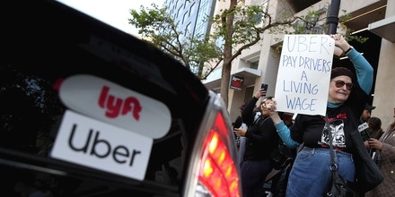 A supporter of Uber and Lyft drivers holds a sign during a protest in front of Uber headquarters in San Francisco on May 8, 2019.