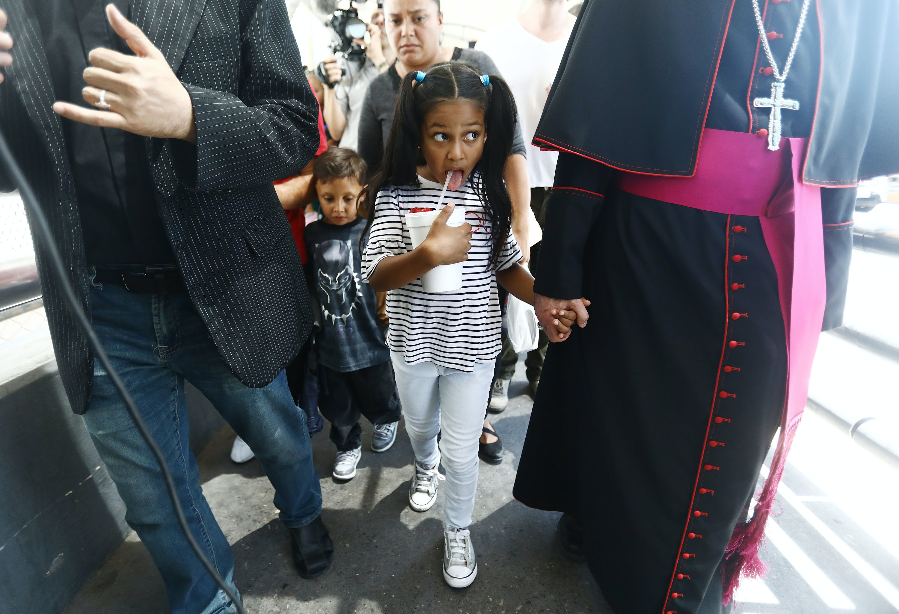 CIUDAD JUAREZ, MEXICO - JUNE 27: El Paso Bishop Mark Seitz (R) escorts Celsia Palma (C), 9, from Honduras, as they cross the Paso Del Norte Port of Entry bridge towards the U.S. on June 27, 2019, in Ciudad Juarez, Mexico. Seitz escorted Celsia and other family members across the port of entry to be processed by U.S. immigration authorities. Earlier, Seitz and clergy from the Diocese of Ciudad Juarez held a prayer with migrants who were recently returned to Ciudad Juarez from El Paso because of the controversial 'Remain in Mexico' policy.