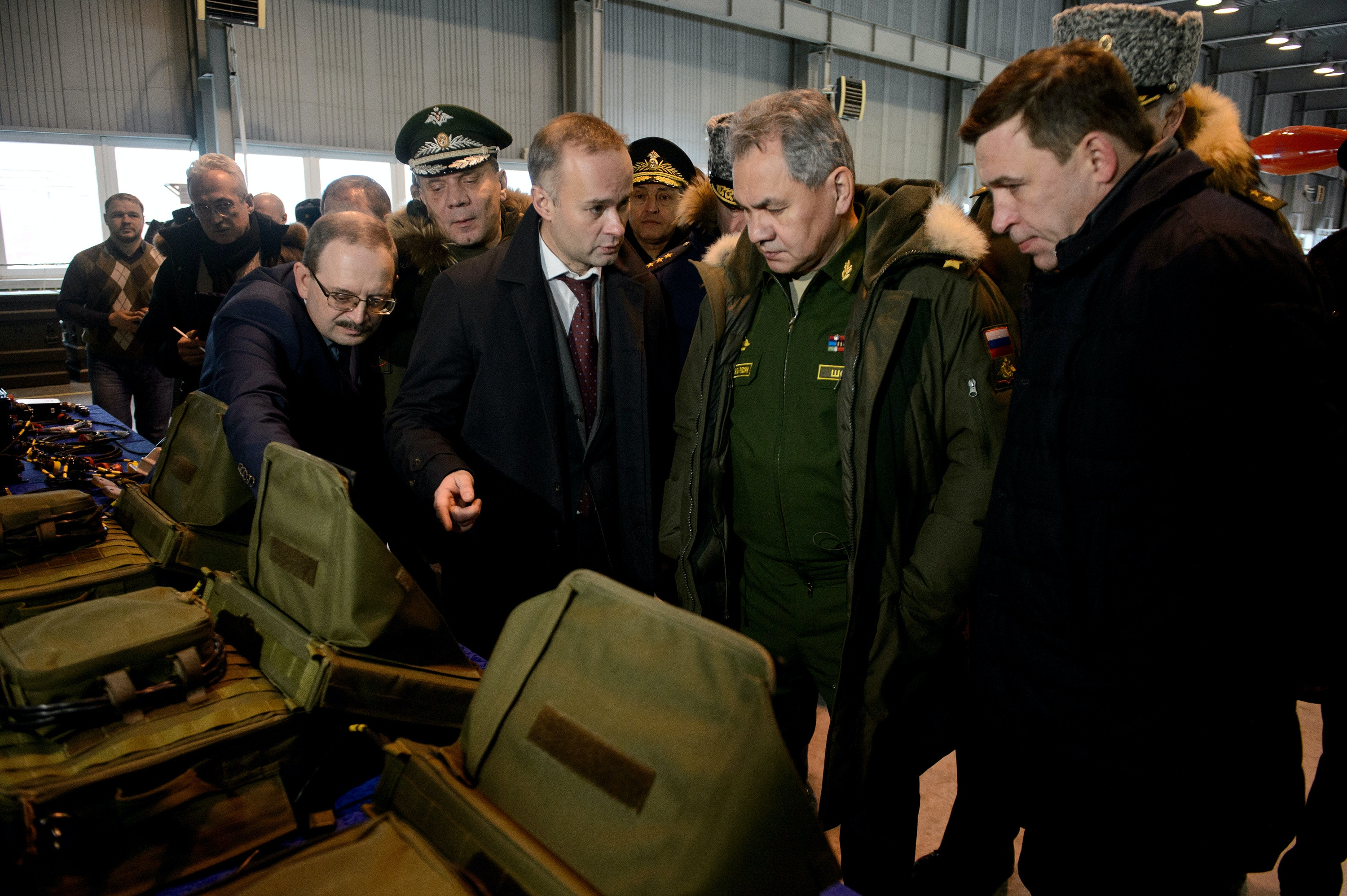 YEKATERINBURG, RUSSIA - JANUARY 20, 2017: Russia's minister of defence Sergei Shoigu (2nd R) and Sverdlovsk Region governor Yevgeny Kuivashev (R) examine the Forpost complex of UAVs (drones) for reconnaissance and target designation, at Ural Works of Civil Aviation (UWCA). UWCA can start supplying Forpost UAVs in 2019. Donat Sorokin/TASS