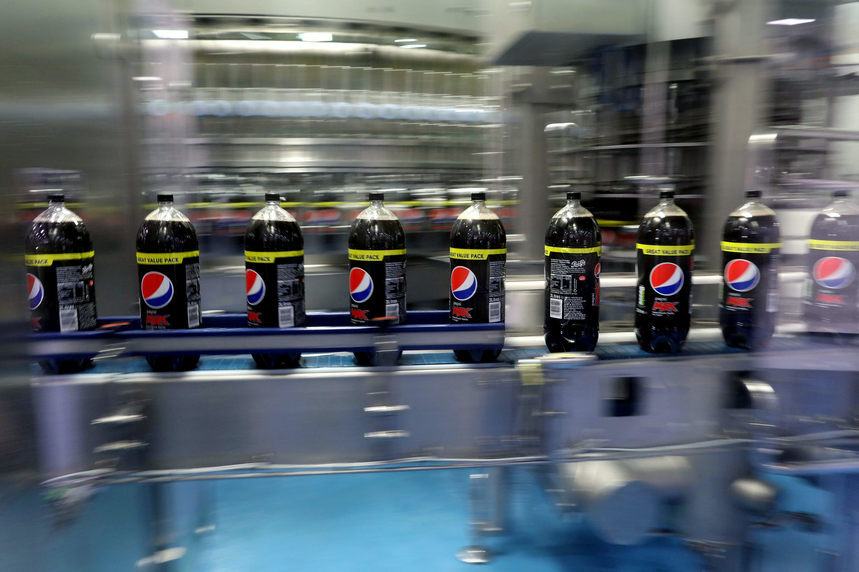 Bottles of Pepsi Max travel along the production line at the Britvic Plc factory and warehouse in Leeds, U.K., on Monday, Jan. 23, 2017. Britvic has agreed in principle to acquire Brazils Bela Ischia Alimentos Ltda, a producer of liquid concentrates and ready to drink juices. The company was founded in 1967 and is based in Astolfo Dutra, Brazil. Photographer: Chris Ratcliffe/Bloomberg via Getty Images