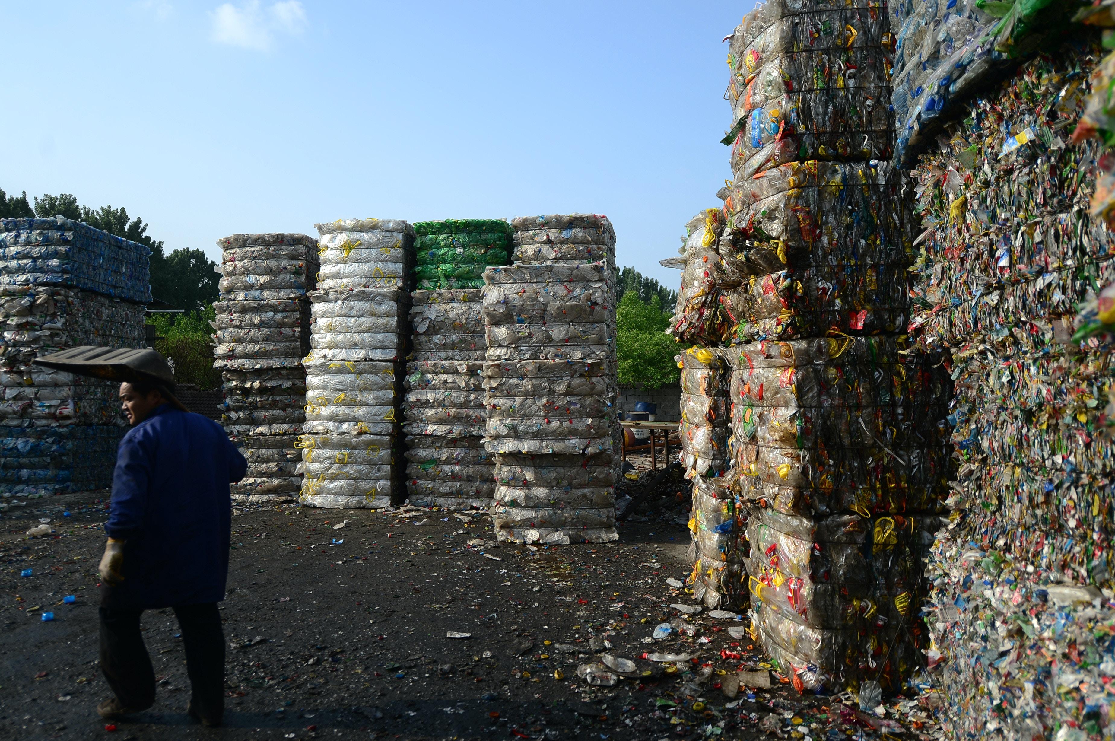 Um trabalhador chinês passa por pilhas de garrafas plásticas em uma estação de reciclagem na cidade de Ji'nan, na província de Shandong, no leste da China, em 4 de maio de 2017.