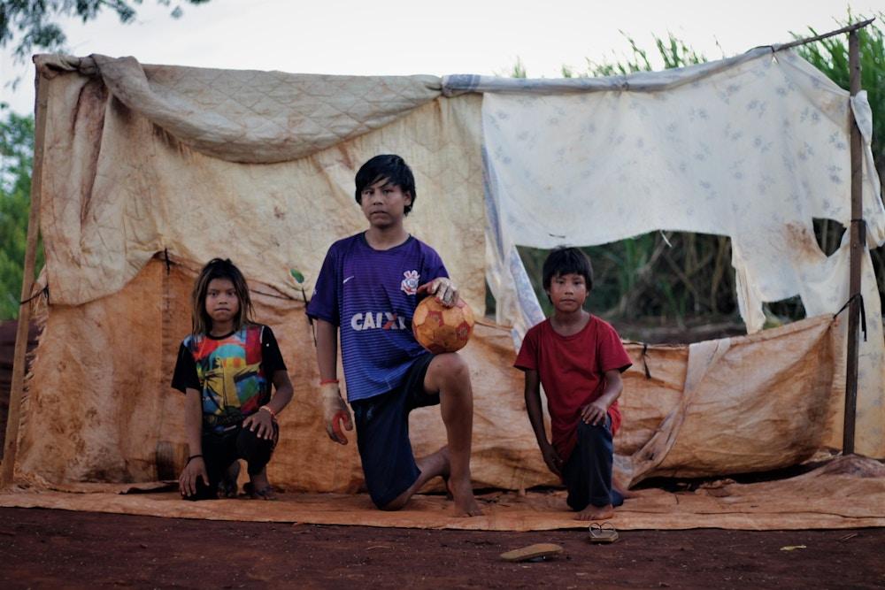 Da esquerda para a direita, a neta e dois netos de Damiana posam para foto após brincarem de gol a gol, única diversão possível no pequeno terreno à margem da rodovia, em Mato Grosso do Sul. A criança do meio é o neto criado como filho por ela– o pai da criança morreu atropelado.