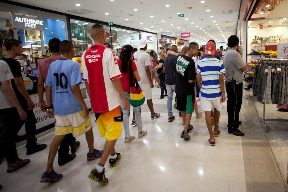 """Participantes de """"rolezinho"""" caminham pelo shopping Metrô Itaquera, zona leste de São Paulo (SP), em 2014. O encontro, marcado pelo Facebook, estava proibido mediante liminar da justiça. Foto: Bruno Poletti/Folhapress."""