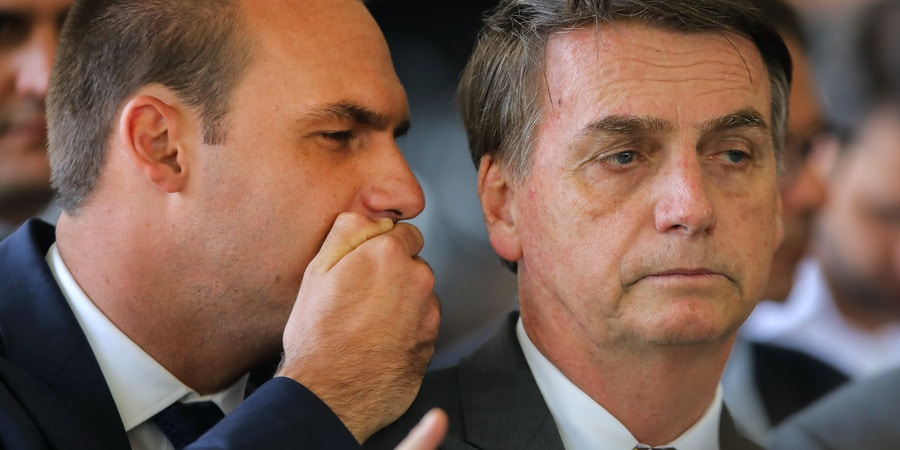 President-elect Jair Bolsonaro (R) listens to his son Eduardo Bolsonaro (L) at the headquarters of the transitional government in Brasilia, on November 14, 2018. - Bolsonaro did the eighth ministerial appointment since winning the presidential election at the end of last month. (Photo by Sergio LIMA / AFP)        (Photo credit should read SERGIO LIMA/AFP/Getty Images)