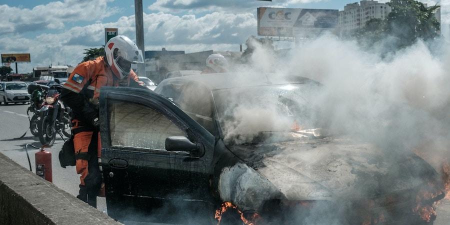 Bombeiro apaga incêndio em carro acidentado na Avenida Brasil, no Rio de Janeiro, em 2017.